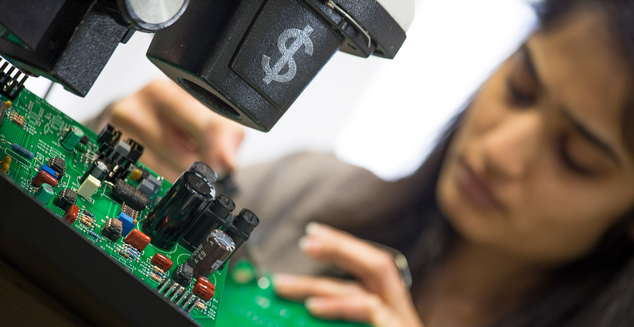 An image of an EMSCO product designer working on a PCB board.